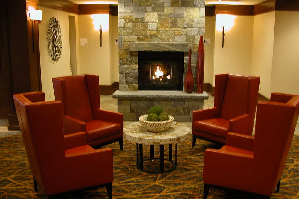 Lobby with 3 Red chairs and Fireplace